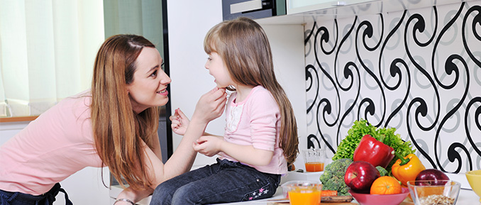 Mom and Daughter Sitting on Counter with Vegetables Epigenetics